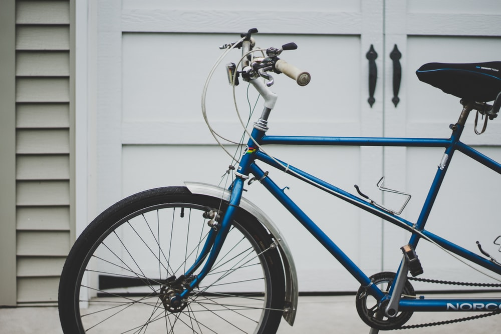 Blue Fixed Gear Bicycle Sitting Outside of White Garage Doors