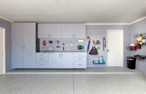 Garage interior with white cabinets and wall storage and a speckled epoxy concrete floor