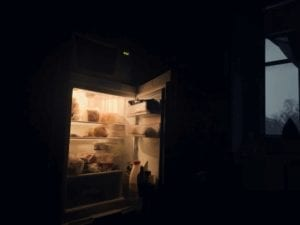 Refrigerator with its Door Open and Illuminated Interior in a Dark Room