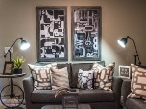 Small Basement Living Room Space with Two Gray Couches and Black and White Wall Art