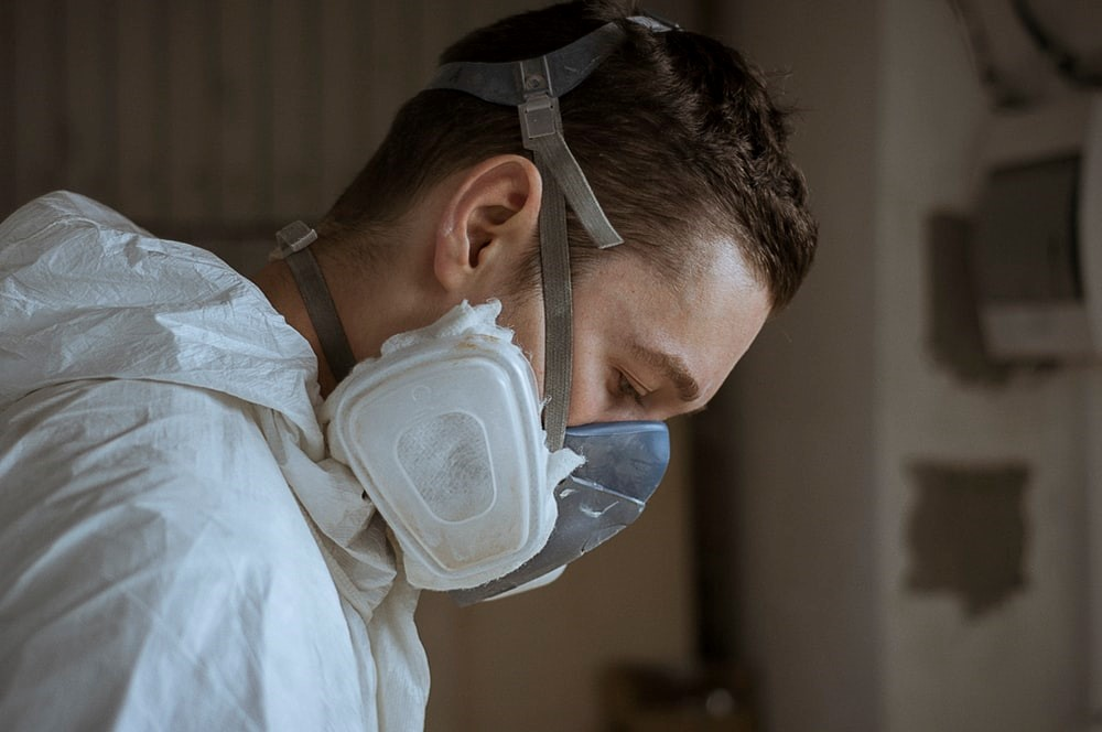 A Contractor in a Heavy-Duty Mask and Protective Gown Looks Down at His Project