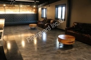 A picture of a room with sofas and two tables with metallic epoxy flooring