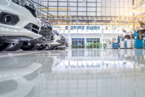 A line of cars inside a building with shiny, white epoxy flooring.